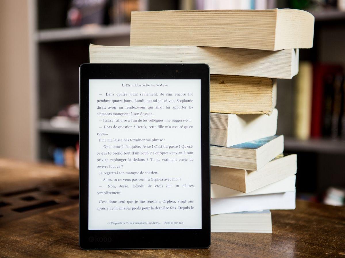 電子書籍と積まれた紙製の本