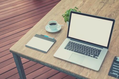 テーブルの上にあるパソコンとコーヒー