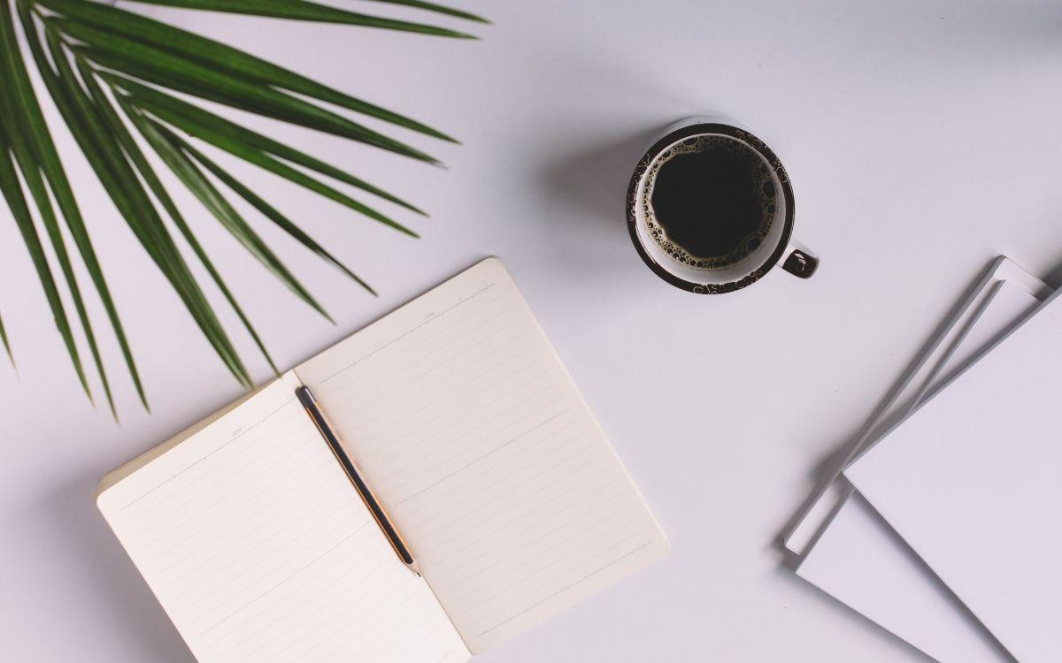 テーブルに置かれたメモ帳とコーヒー