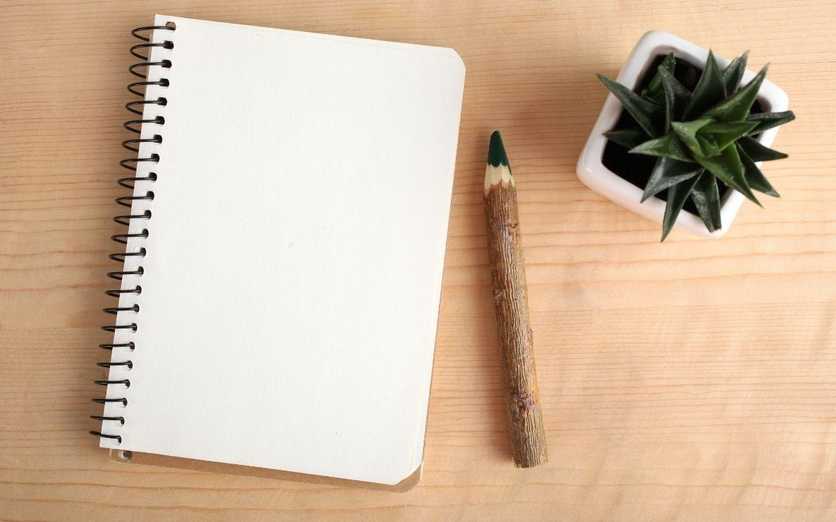 テーブルの上に置かれたノートと鉛筆