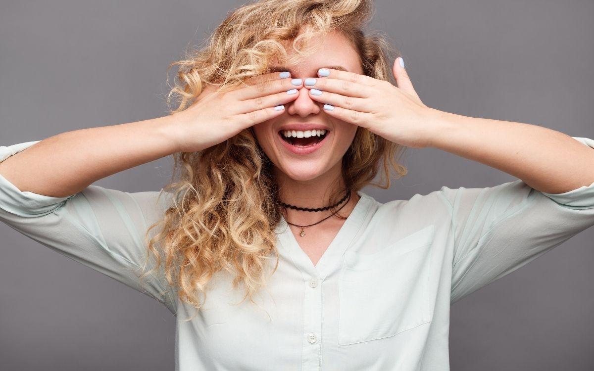 目隠しをしながら笑う女性