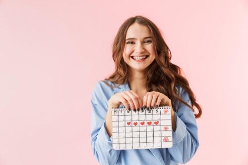 生理日カレンダーを持ってほほ笑む女性