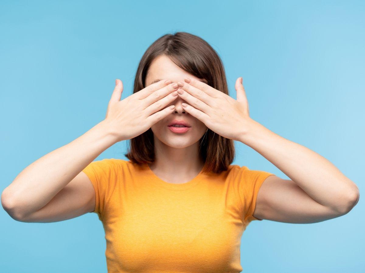 手のひらで目を隠す女性
