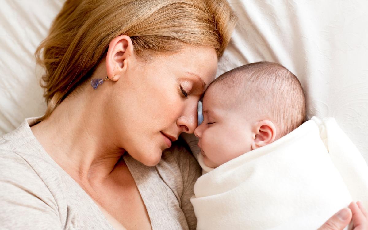 ベッドで眠る母親と赤ちゃん
