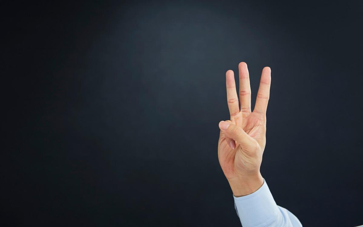 3本の指を立てる手