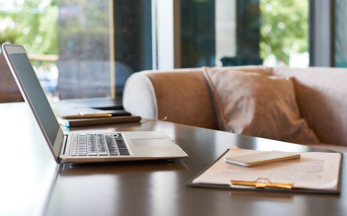 カフェのテーブルに置かれたパソコンとノート