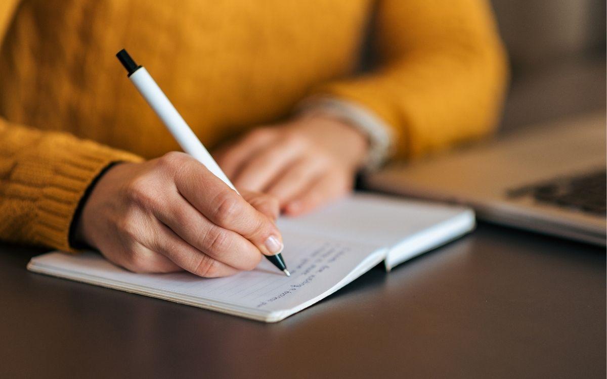 ノートの文章を書く女性