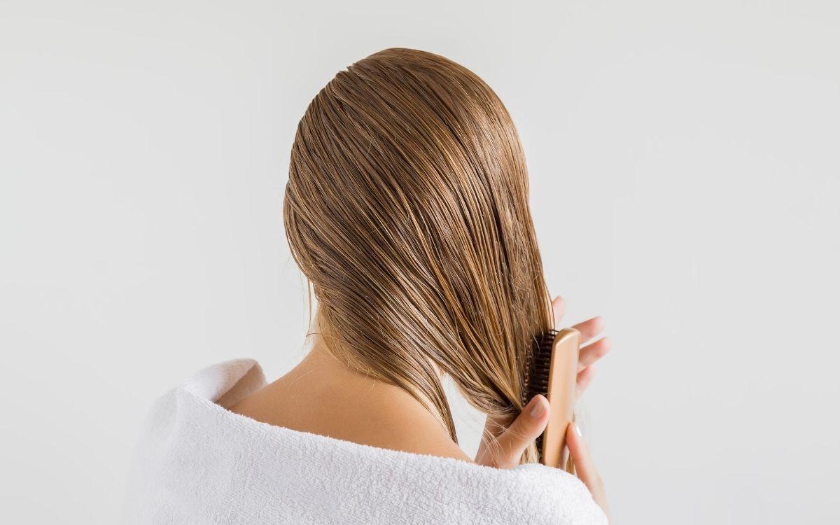 ヘアオイルを髪に塗る女性