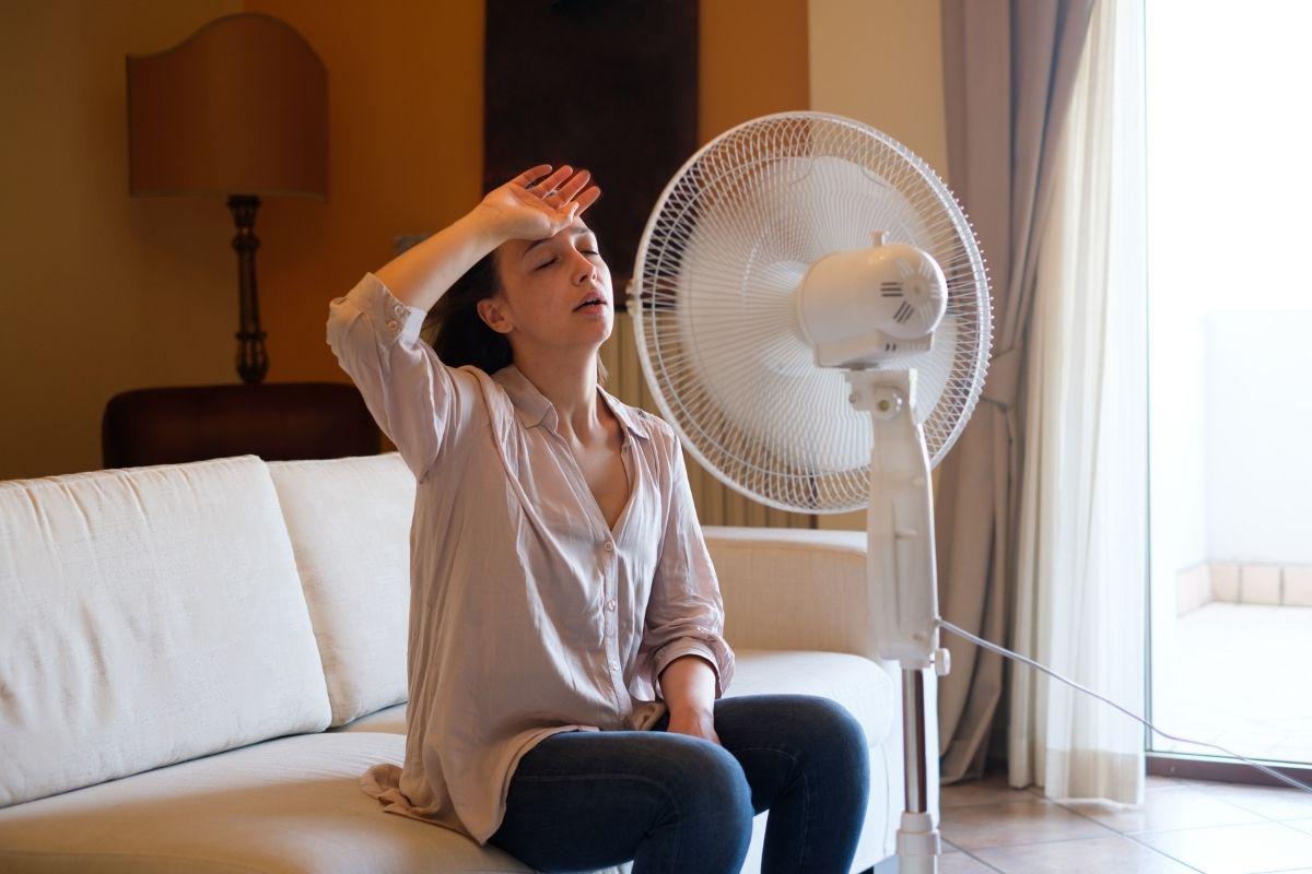 扇風機の風に当たる女性